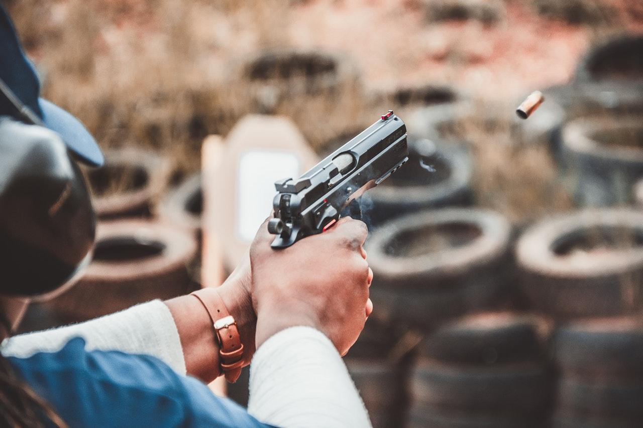 Man firing a black gun