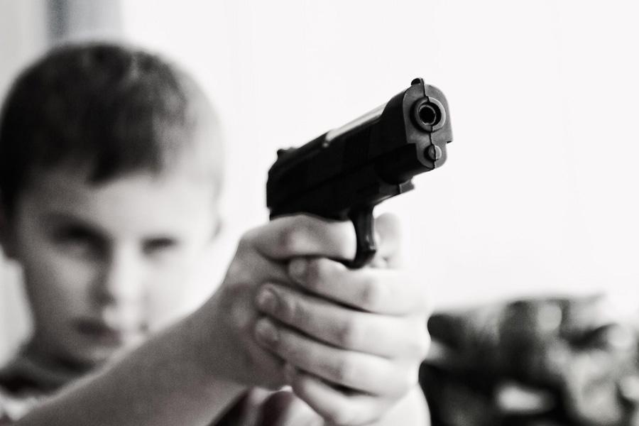 A boy holding a gun attempting to shoot